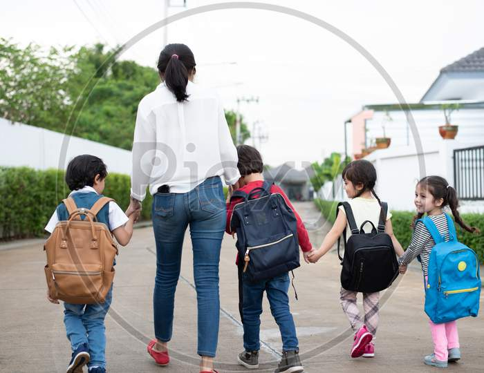 Group Of Preschool Student And Teacher Holding Hands And Walking To Home. Mom Bring Her Children Go To School Together. Back To School And Education Concept. People And Lifestyles Theme. Back View