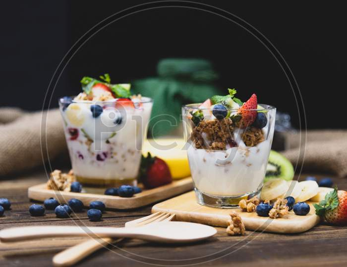 Healthy Greek Yogurt With Granola And Mixed Berries On Wooden Table And Many Fruits. Food And Dessert Concept.