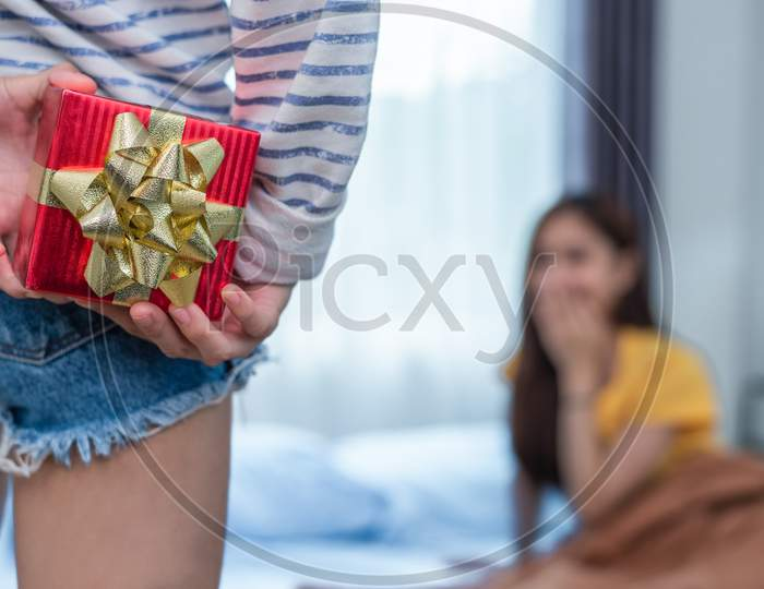 Close Up Of Woman Hands Holding Gift For Surprise Her Girlfriend In Bedroom. Person And People Concept. Lifestyles And Happiness Life Concept. Lesbian And Homosexual Theme.