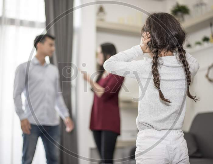 In Back View, Little Girl Puts Her Hands On Her Ears Because She Does Not Want To Hear Her Dad And Mom Quarrel. Close Ears, Family Dramatic Scene, Parrents Issues, Social And Parents Problem Concept