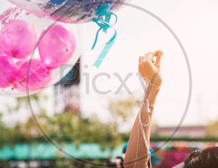 Hand Holding Up Rope Of Greeting Balloon For Special Event Or Birthday Party. Happiness And Celebration Party Concept. Friendship Congratulation And Happy People Theme. Graduated Event Theme