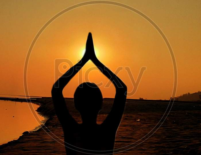 Yoga, silhouette woman doing yoga practice or exercise in the sunset Sky background, international yoga day concept