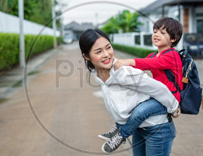 Single Mom Carrying And Playing With Her Children Near Home With Villa Street Background. People And Lifestyles Concept. Happy Family And Home Sweet Home Theme. Outdoors And Nature Theme.