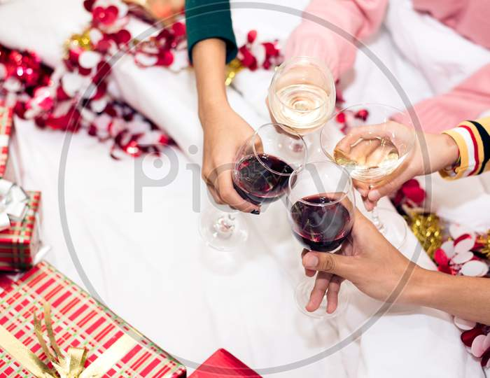 Hands Of People Celebrating New Year Party In Home With Wine Drinking Glasses. New Year And Christmas Party Concept. Happiness And Friendship Concept. Relation And Funny Together Theme. Clinking Glass