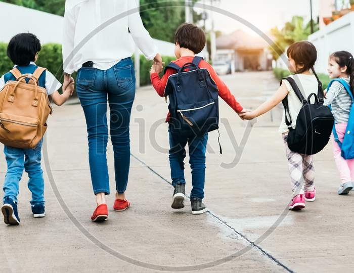 Back To School Students Mother Group Going School Together. Parent Send Little Boy And Girl For First Class Semester Term With Schoolbag Or Satchel Together. Collaborative Learning And Empathy Daycare