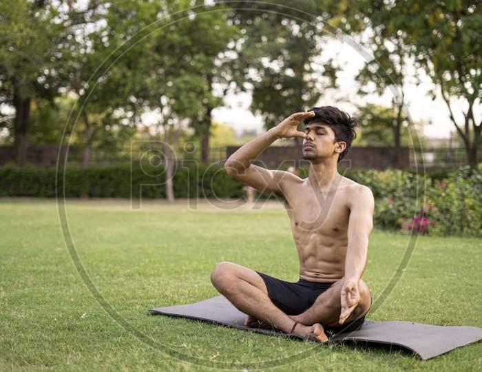 A Young Indian Shredded Teenage Boy Doing Yoga Aasan In The Park On International Yoga Day, Anulom Vilom Aasan.