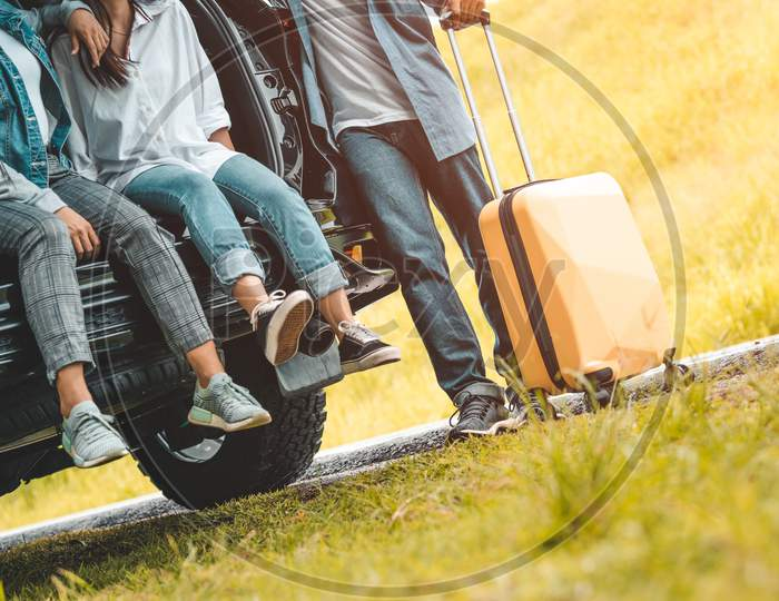 Closeup Lower Body Of Group Of Friends Relaxing On Suv Car Trunk With Trolley Luggage Along Road Trip With Autumn Mountain Hill Background. Freedom  Road Way. People Lifestyle Transportation Travel