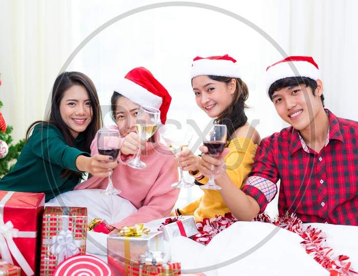 Group Of Young Asian People Celebrating New Year Party In Home With Wine Drinking Glasses. New Year And Christmas Party Concept. Happiness And Friendship Concept. Relation And Funny Together Theme.