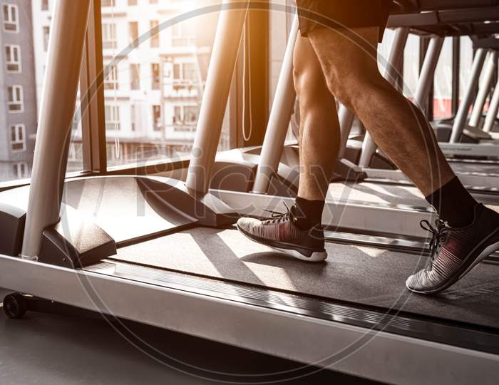 Close Up Of Sport Man Running On Treadmill In Fitness Gym At Condominium In Urban. People Lifestyles And Sport Activity Concept.