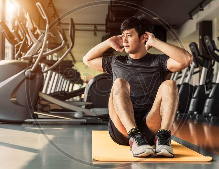 Sport Man Doing Crunch Or Sit Up Posture On Yoga Mat In Fitness Gym At Condominium With Gym Equipment Background. Office Working People Lifestyles And Sport Workout Concept.