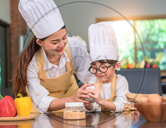 Beautiful Asian Woman Teaching Cute Little Boy With Eyeglasses To Drink Milk In Kitchen At Home Together. Lifestyles And Family. Son Dislike Milk And Doing Funny Face With Milk Glass. Food And Drink