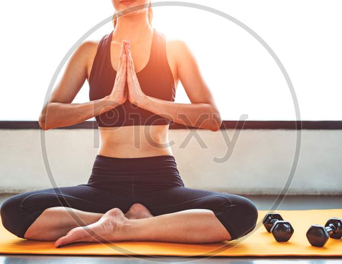 Front View Beauty Woman Doing Yoga And Raise Hand Or Pay Obeisance In Fitness Workouts Training Gym Center.  Lifestyle Sport Woman Sitting On Mat With Sport Equipment And Exercise Dumbbells Background