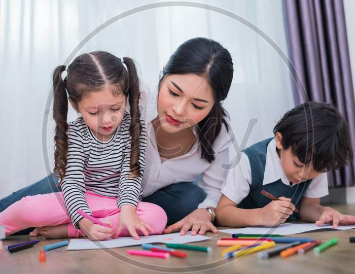 Mom Teaching Children In Drawing Class. Daughter And Son Painting With Colorful Crayon Color In Home. Teacher Training Students In Art Classroom. Education And Learning Development Of Kids Theme.