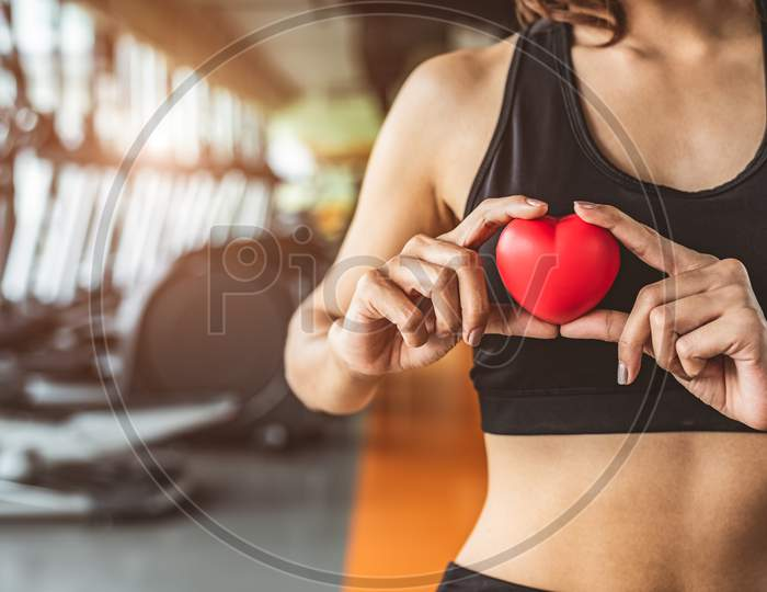 Happy Sport Woman Holding Red Heart In Fitness Gym Club. Medical Cardio Heart Strength Training Lifestyle. Pretty Female Sport Girl Workout Exercise. Cardiac Healthy And Well-Being. Massage Ball In Hand