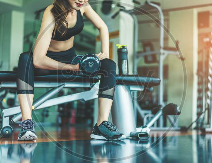 Asian Young Woman Playing Dumbbell Workout Exercise In Fitness Gym. Relax And Health Care Concept. Sports And Weight Training Theme.
