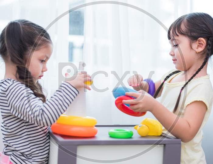 Two Cute Caucasian Girls Playing Toys Together In Home. Kids Development And Leisure Concept. Home Sweet Home And Happy Family Theme.
