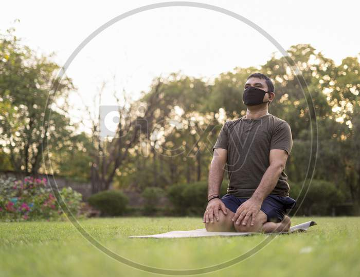 Mid-Aged Man Doing Yoga In A Park Covered With Trees On International Yoga Day.