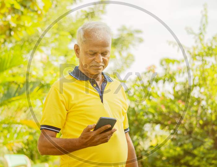 Senior Man Looking The Phone - Old Male Person Using Mobile At Park - Elderly Citizen On Smartphone Outdoor.