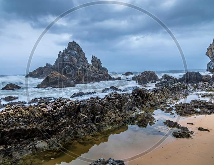 Long Exposure of rocks at the beach of the Camel Rock bay in New South Wales, Australia at a cloudy and windy day in summer with strong waves in the ocean.