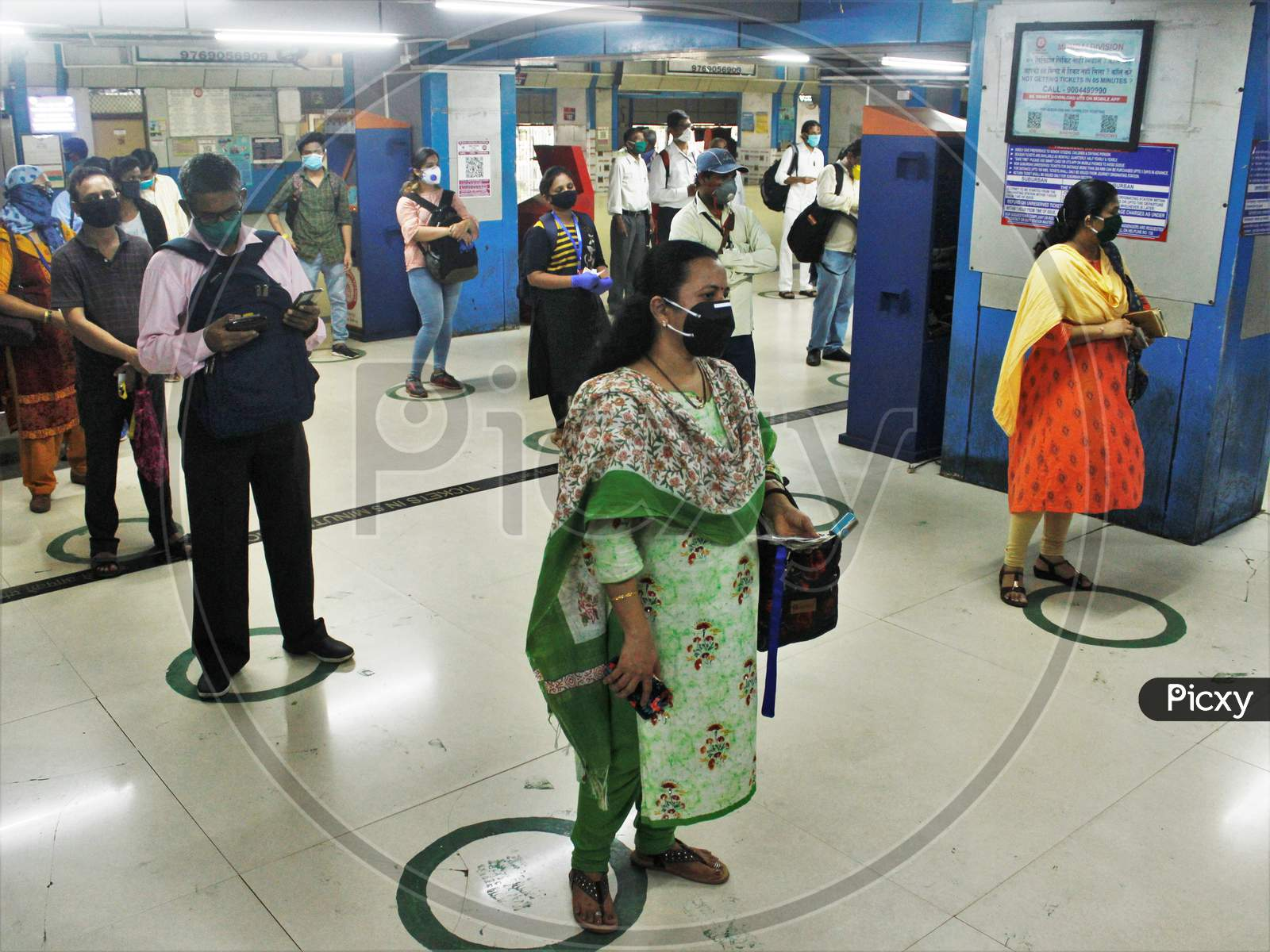 Commuters Stand Inside Circles To Maintain Social Distancing As They Wait To Buy Local Train Tickets, After The Government Eased A Nationwide Lockdown That Was Imposed As A Preventative Measure Against The Covid-19  Coronavirus , At Churchgate Station, In Mumbai, India On June 16, 2020.