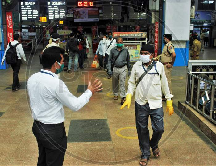 A railway official asks the commuters to show their ID cards before they board the trains, at Churchgate station, after the government eased a nationwide lockdown that was imposed as a preventive measure against the COVID-19 coronavirus, at Churchgate station, in Mumbai, India, on June 16, 2020.