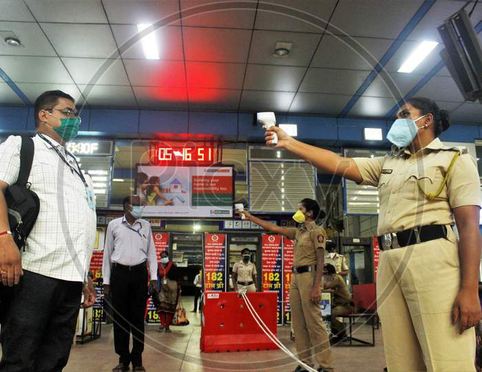 Police personnel check the temperature of the essential service workers going to board the train,  after the government eased a nationwide lockdown that was imposed as a preventive measure against the COVID-19 coronavirus, at Churchgate station, in Mumbai, India, on June 16, 2020.