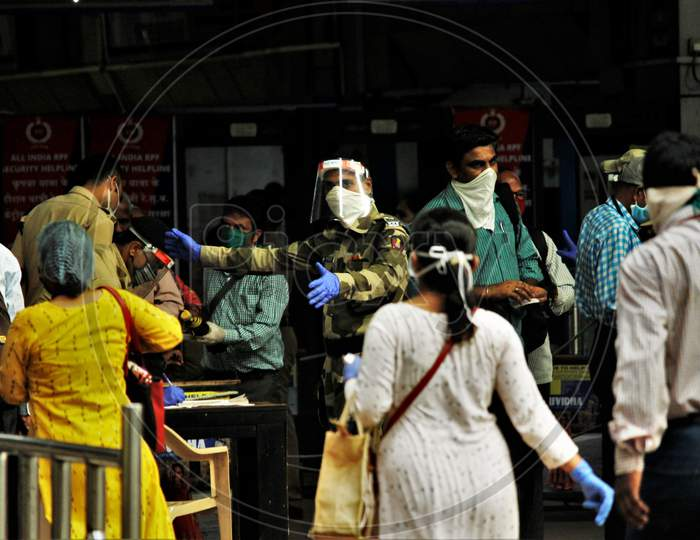 A CRPF official instructs the commuters to maintain social distancing, at Churchgate station, after the government eased a nationwide lockdown imposed as a preventive measure against the COVID-19 coronavirus, at Churchgate station, in Mumbai, India, on June 16, 2020.