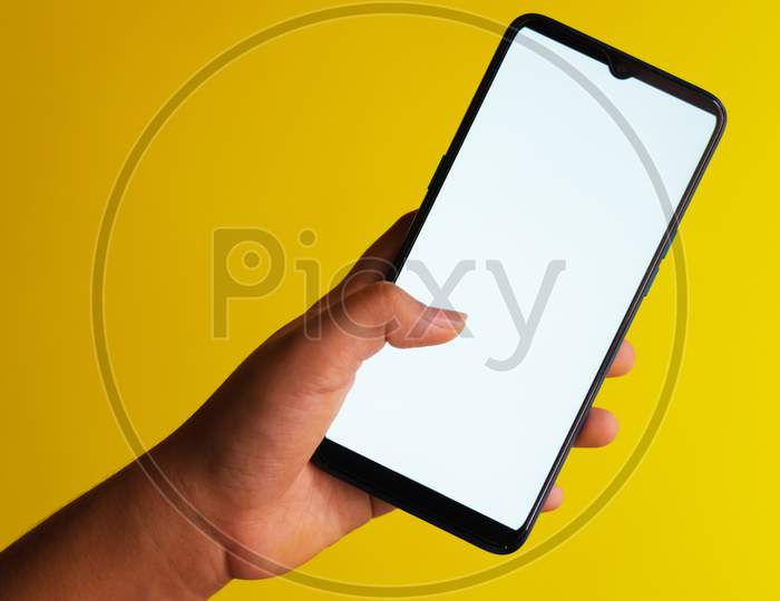 Finger tapping on a smartphone with white screen held against a plain yellow background with copy space