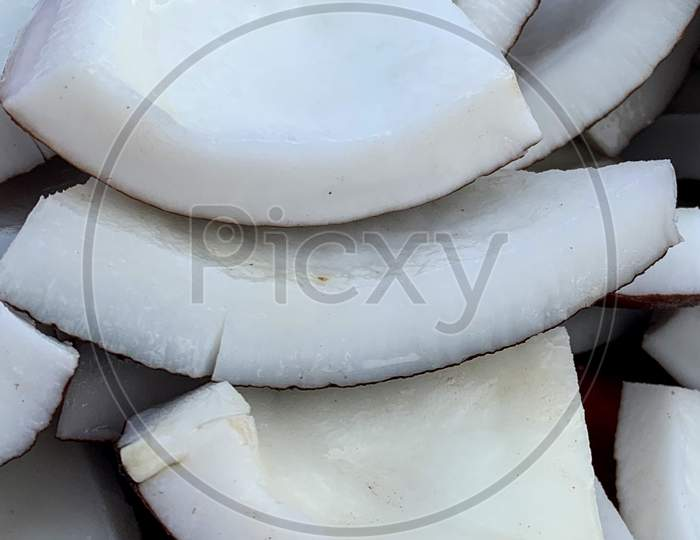 Pile Of Fresh Mature Coconut Pieces Kept For Sale In Market In India.