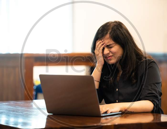 Depressed young Indian girl while working on a laptop
