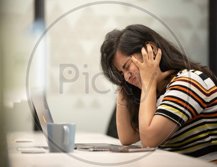 Depressed working woman crying at work