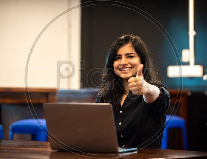 Smiling Young Indian woman showing thumbs up gesture as she works on a Laptop