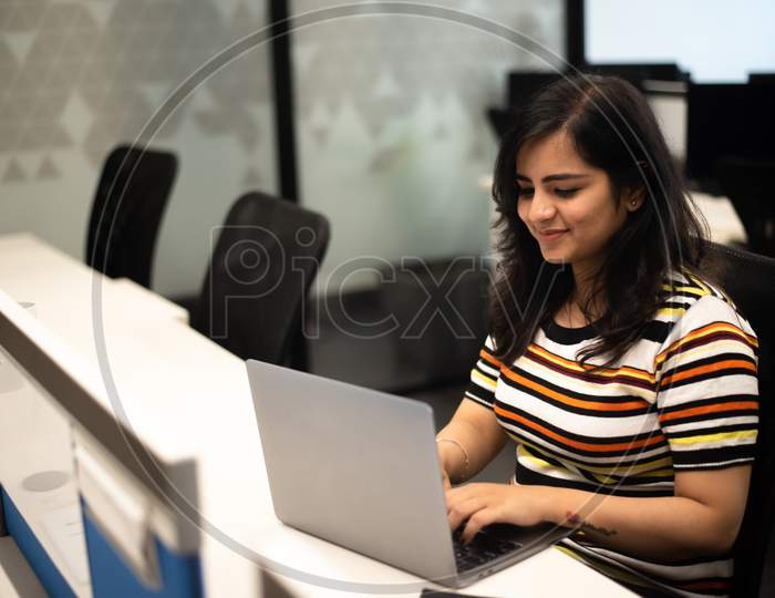 Smiling young Indian girl working in an Office.