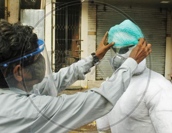 A shopkeeper adjusts the cap of a PPE kit makeshift mannequin, in Mumbai, India on June 20, 2020.