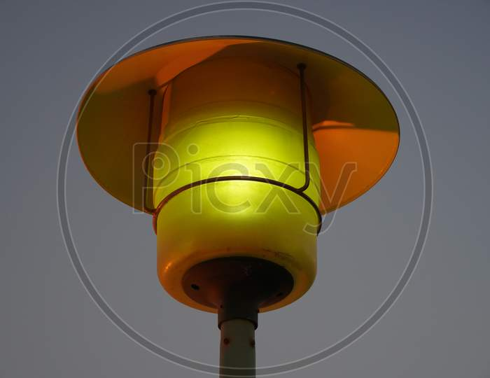 Street Lamp Post With The Evening Skyline View. Outdoor Light Fixture With Sky Background. A Single Hooded Street Light.