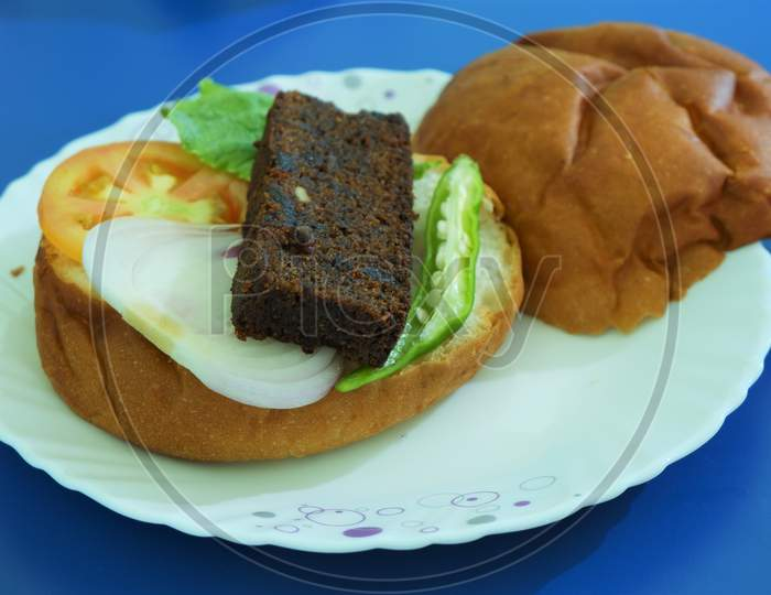 stuffed big burger on white plate and blue background