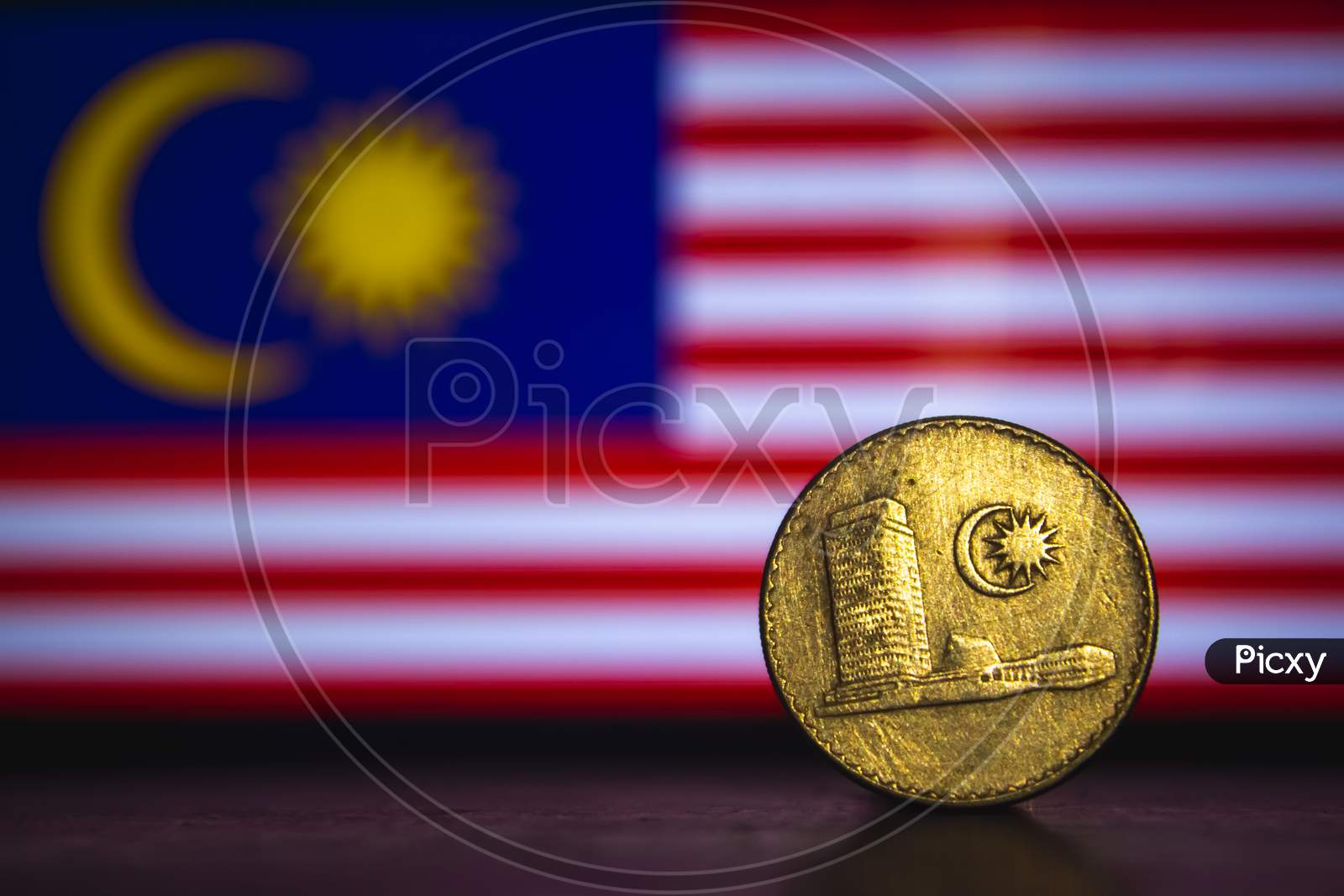 Malaysian Coin - Malaysia 20 Sen 1973 Coin Isolated On Malaysia Flag Background. Malaysian Currency Twenty Sen Coin With Space For Text Copy.