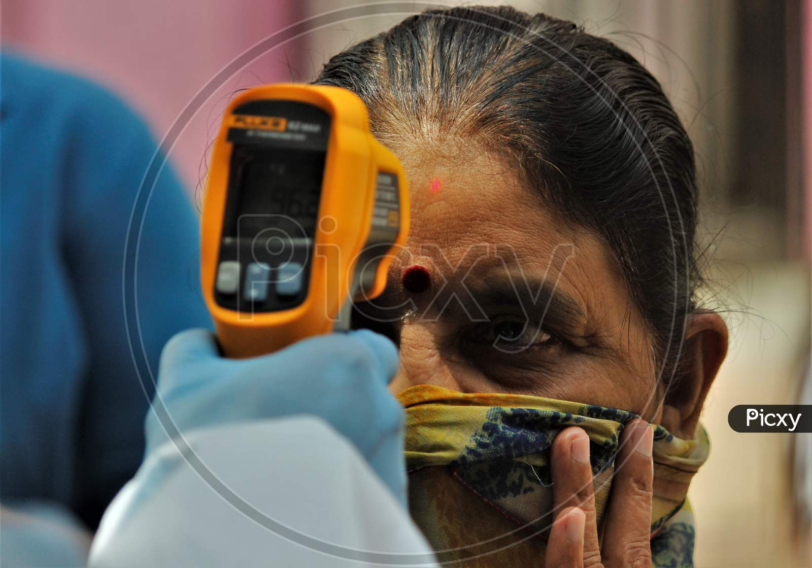 A Health Care Worker Checks The Temperature Of A Resident At Dharavi, One Of Asia'S Largest Slums, As A Preventative Measure Against The Spread Of Coronavirus Disease, In Mumbai, India On June 21, 2020.