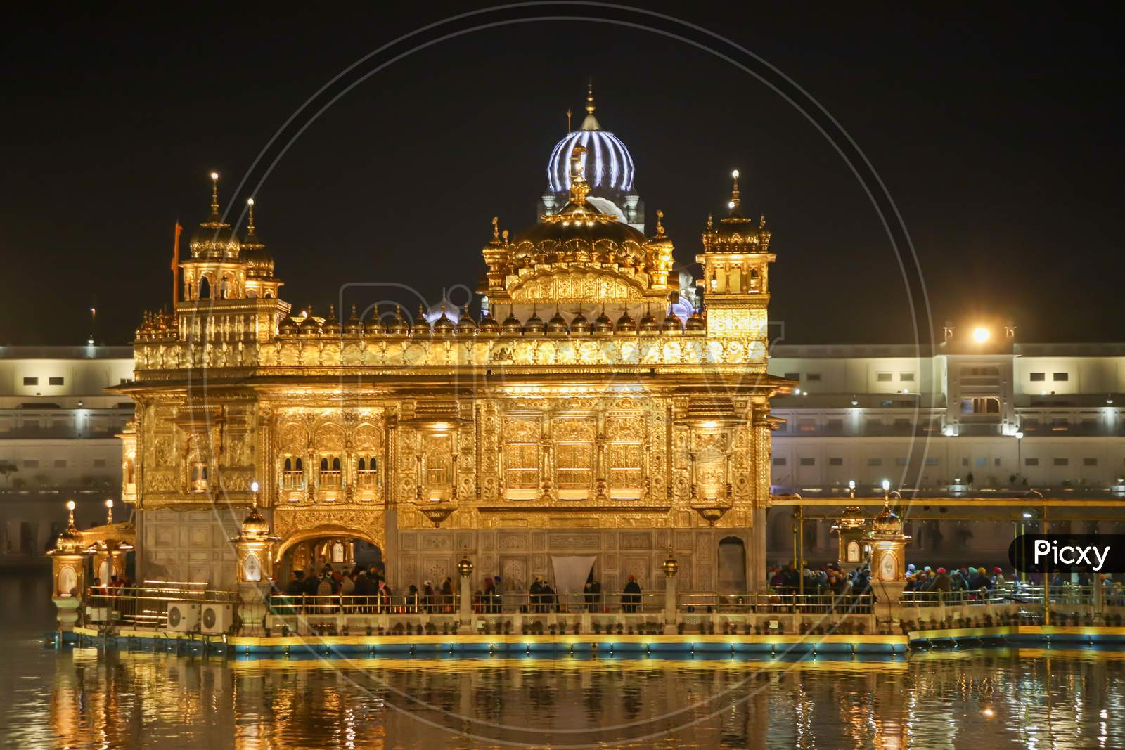Golden Temple With Reflection In The Water At Night