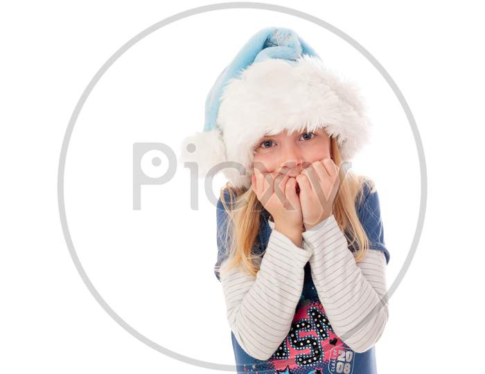 A Young Blonde Girl In A Christmas Hat Waits Nervously For Christmas Day.