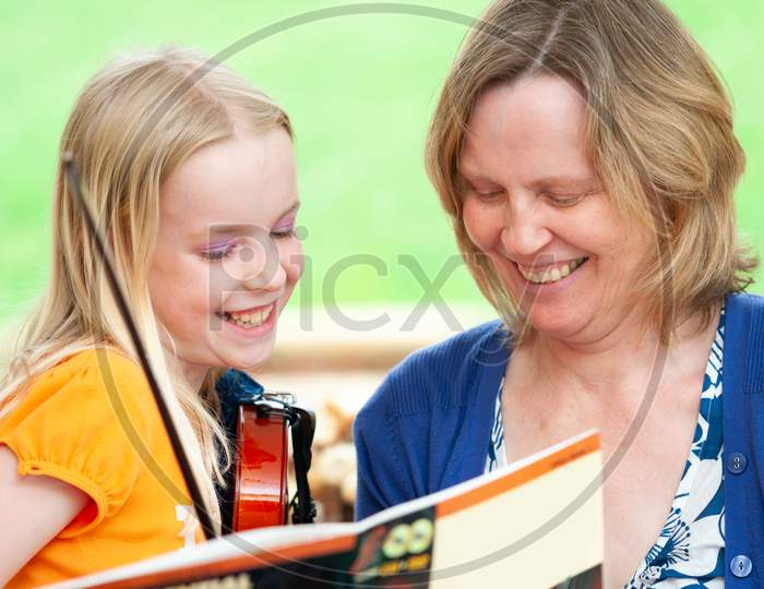 Very Happy Mother And Daughter Learning To Play Violin