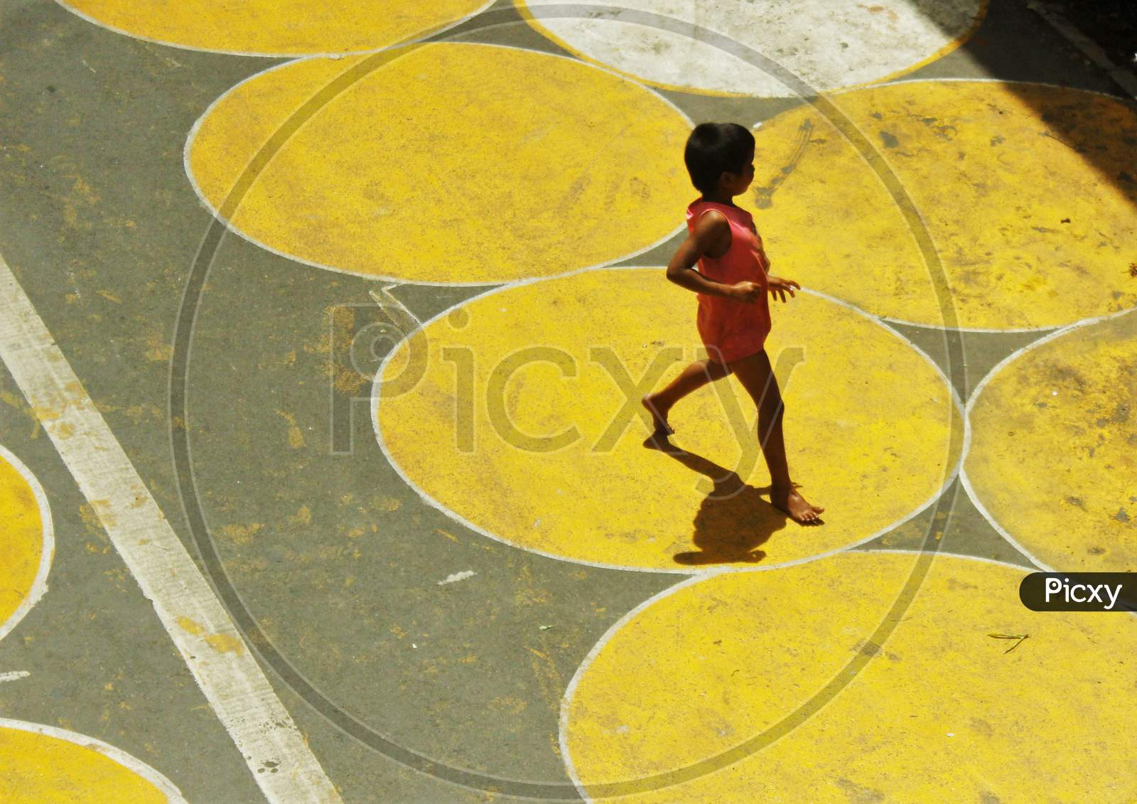 A Kid Runs On The Yellow Circles Painted For Physical Distancing At A Residential-Cum-Market Area, In Mumbai, India On June 29, 2020.