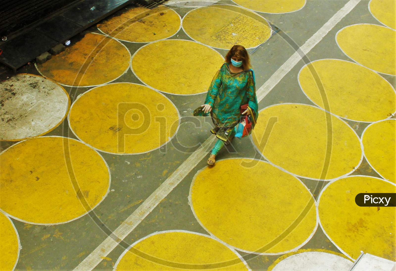 A Woman Walks Past Yellow Circles Painted For Physical Distancing At A Residential-Cum-Market Area, In Mumbai, India On June 29, 2020.