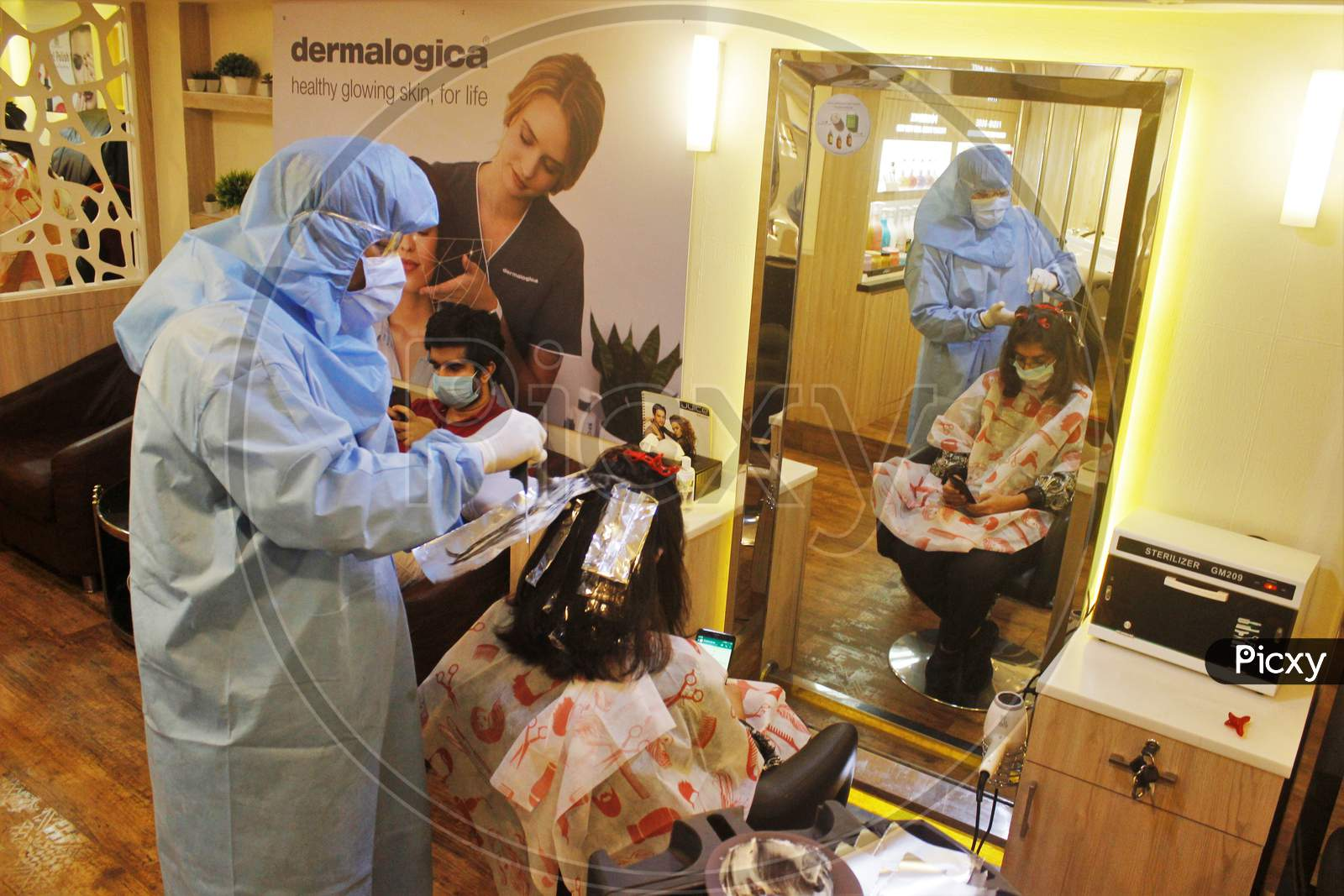 Hair stylists wearing protective gear attend to a customer with face masks at a salon in Mumbai, India, on June 29, 2020.
