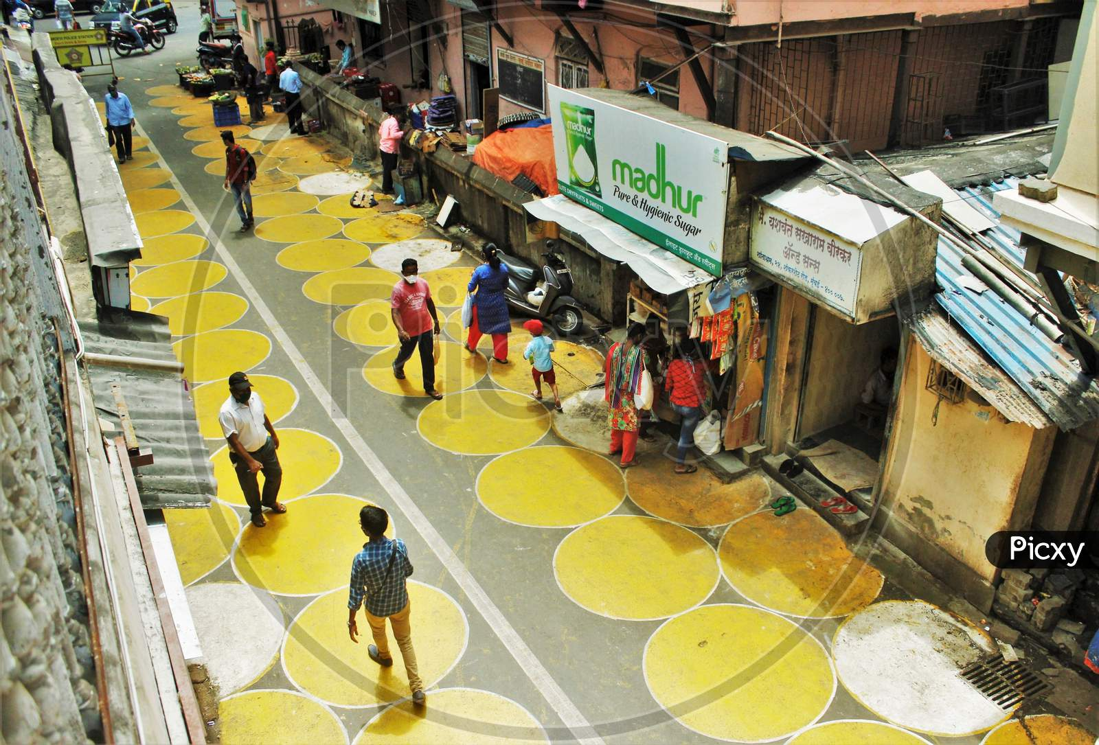 People Walk On Yellow Circles Painted For Physical Distancing At A Residential-Cum-Market Area, In Mumbai, India On June 29, 2020.