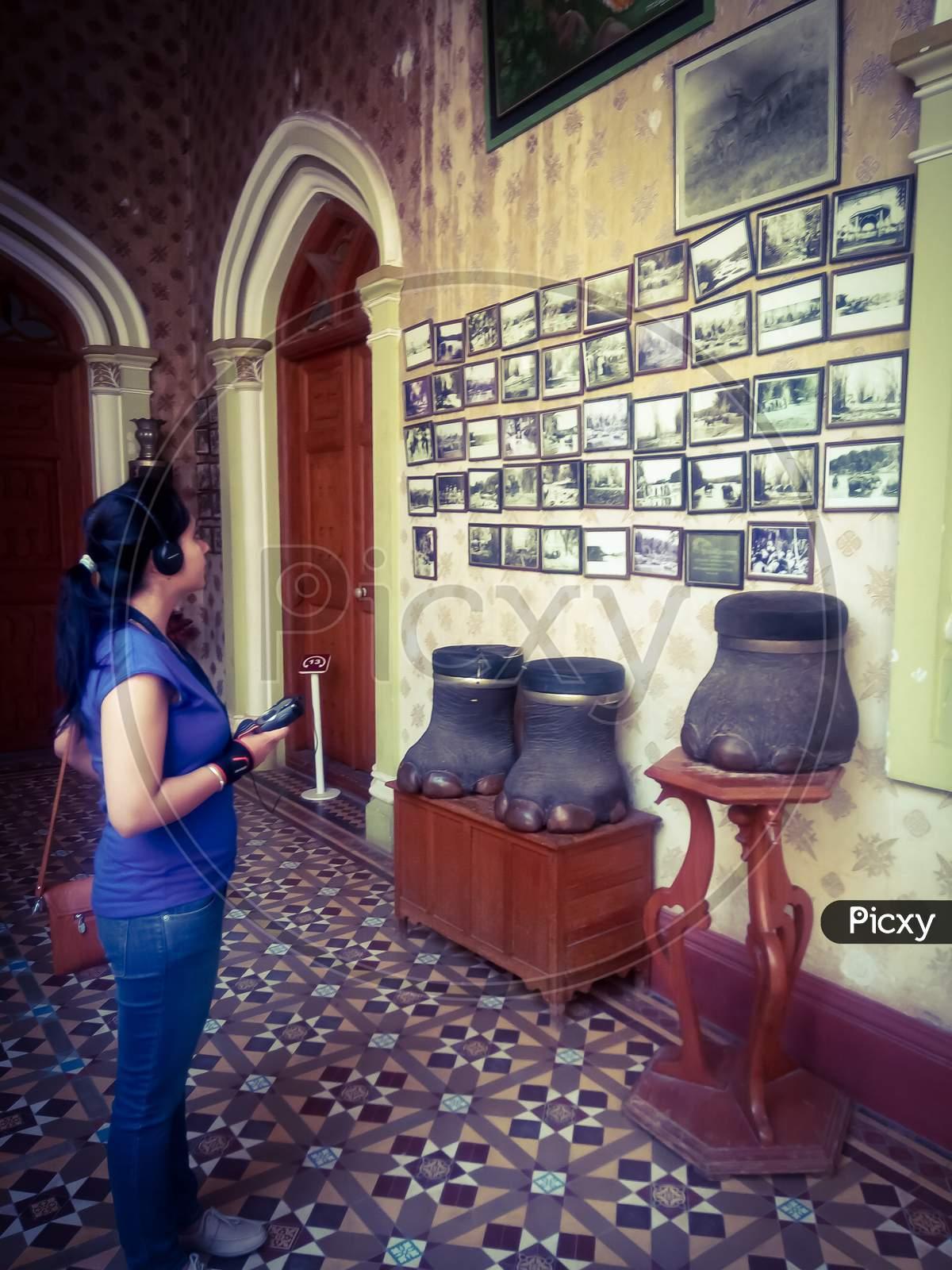 Tourist Observing The Photos Hung On The Wall In Bangalore Palace, Jayamahal Palace In Bangalore Karnataka India.