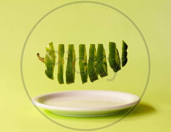 Green Bell Pepper Cut Into Slices Suspended A Plate. Healthy Food Concept.