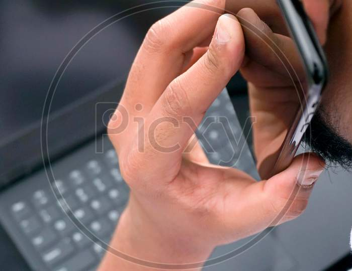 young man using laptop and smart phone together