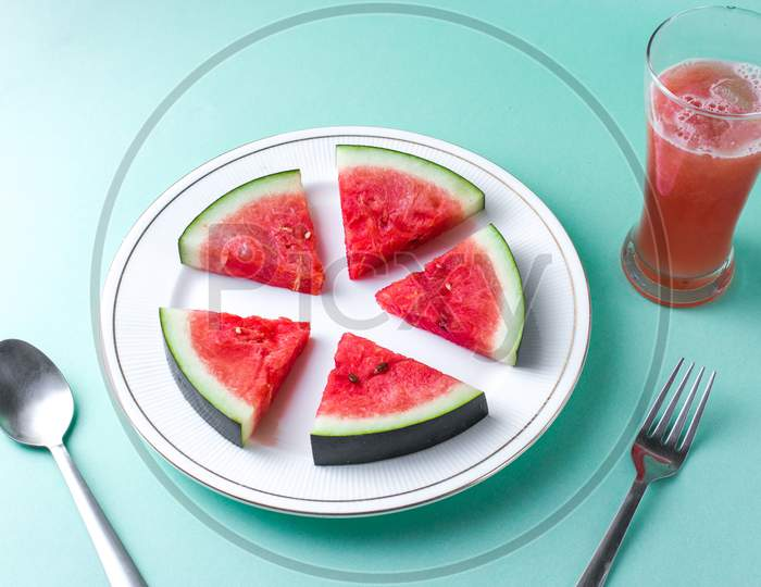 Sliced Watermelon on white plate with spoon and fork stock photo