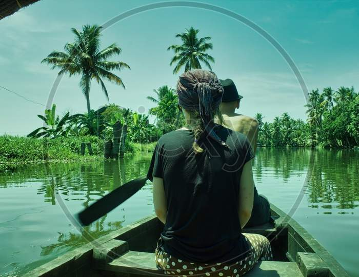A Man Riding A Boat Manually In The Backwaters Of Alleppey